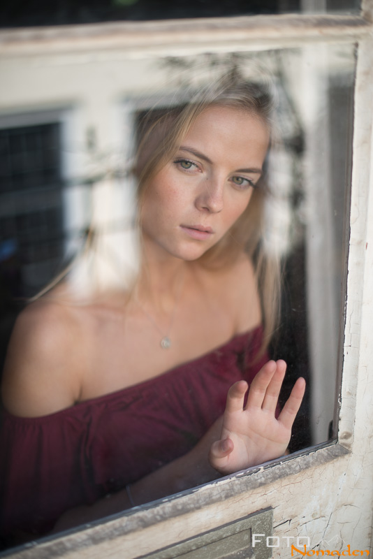 Fotonomaden Portraet durch Fensterscheibe