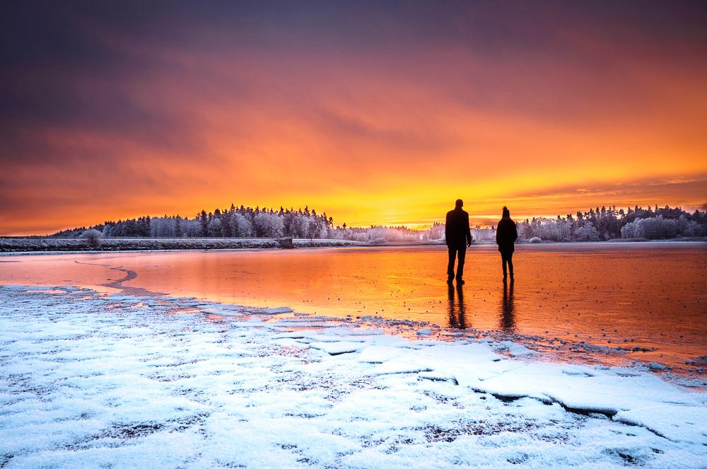 Zwei Personen auf zugefrorenem See bei Sonnenuntergang
