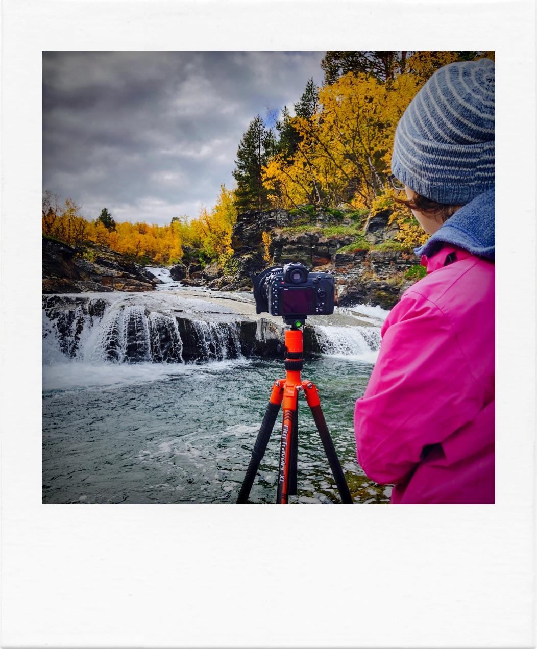 Fotografin mit Stativ in Lappland bei einem Wasserfall bei der Ruska