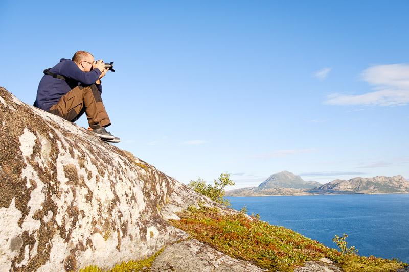 Markus sitzt auf Fels und fotografiert die Landschaft
