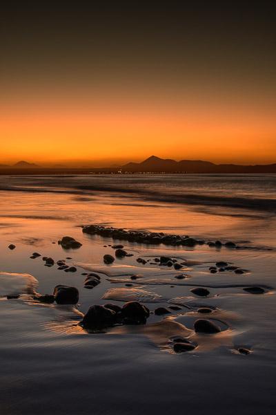 Strand mit kleinen Steinen nach Sonnenuntergang