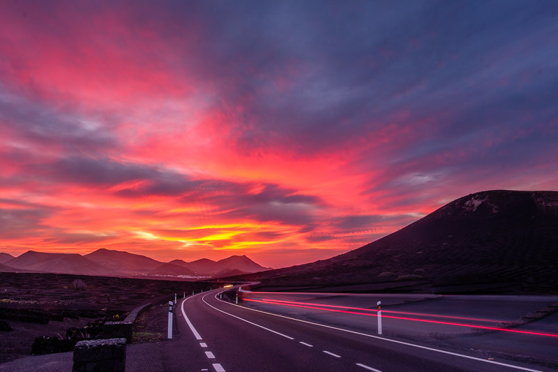 Straße mit verwischten Lichspuren zu Sonnenuntergang