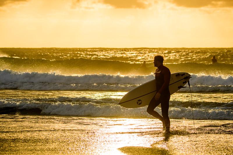 Surfer im Gegenlicht am Strand Fotonomaden