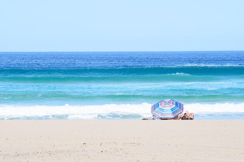 Strandfoto Meer mit buntem Sonnenschirm