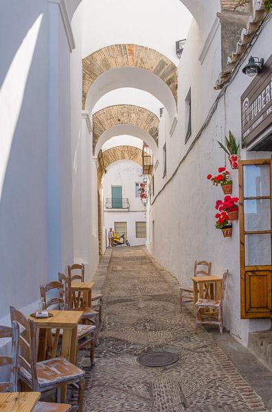 Weiße Gasse mit Cafétischen in Vejer de la Frontera, Andalusien