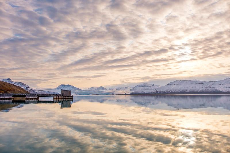 Europareisen Highlight Norwegen: Sonnenaufgang mit Wolkenspiegelung am Meer und Steg