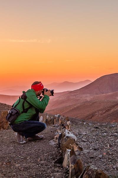 Markus fotografiert bei Sonnenaufgang mit einer Spiegelreflexkamera