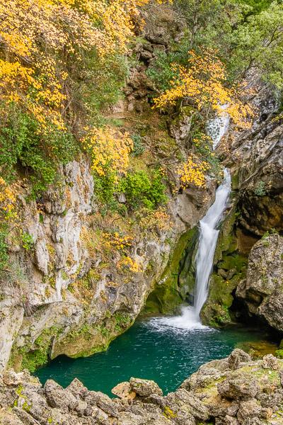 Langzeitbelichtung von Wasserfall in Herbstwald