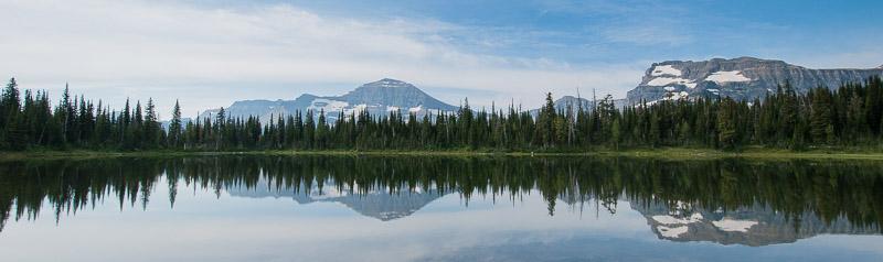 Panoramafoto von Bergkulisse mit Wald mit Spiegelung im See