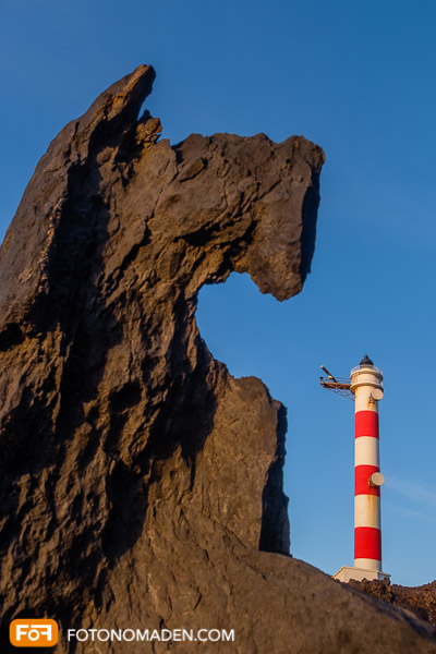 Rot-weißer Leuchtturm neben braunem Fels