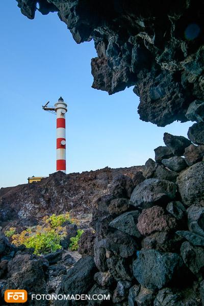 Rot-weißer Leuchtturm von Felsen eingerahmt