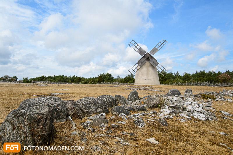 Windmühle mit Steinreihe und blauem Himmel