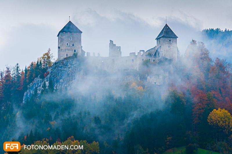 Schöne Herbstbilder: Bur in Nebel mit Herbstwald