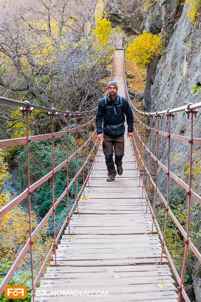 Mann auf Hängebrücke in Herbstwald